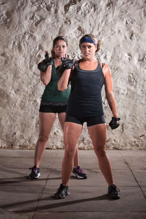 Pretty woman working out and sweating while lifting kettle bell weights Stock Photo - 15934499