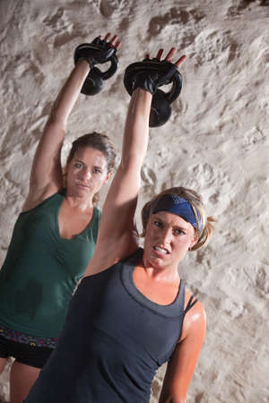 perspiration: Strong ladies pushing up kettle bell weights during boot camp workout Stock Photo