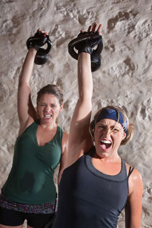 Instense women shout as they push kettle bell weights up