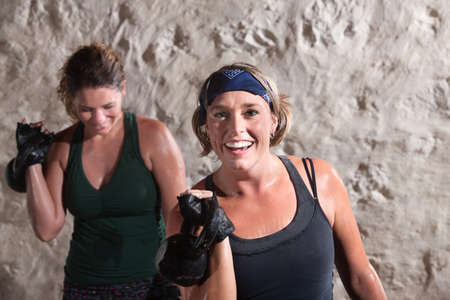 perspiration: Smiling woman with workout partner lifting weights
