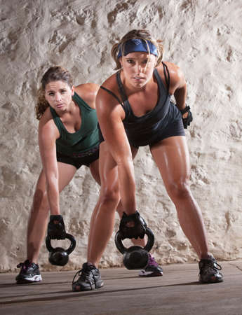 perspiration: Serious pair of young women lifting weights during boot camp workout Stock Photo
