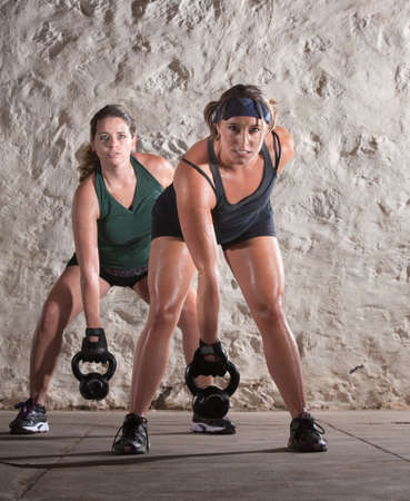 Two European women lifting heavy weights and sweating photo