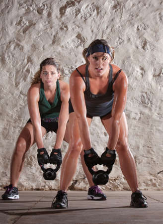 strong: Pretty Caucasian woman lift kettle bell weights with both hands Stock Photo