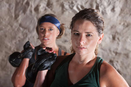 Two serious sweating women holding weights indoors photo