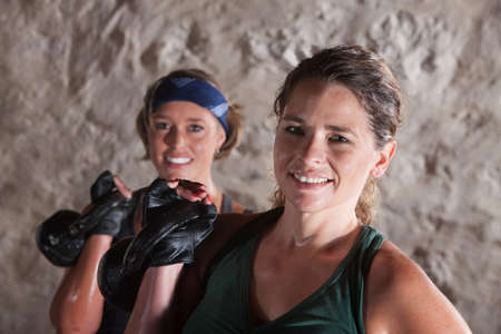 Pair of smiling ladies holding kettlebell weights photo