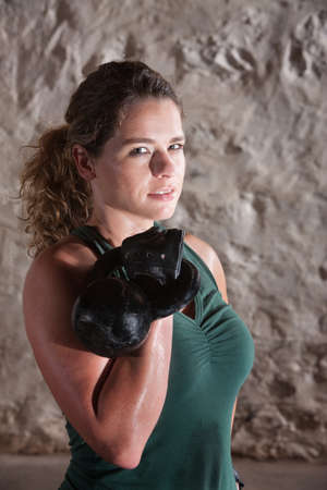 Pretty woman in tank top holding weights and sweating indoors photo