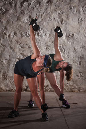 Pair of pretty women lifting kettlebell weights over their shoulders photo