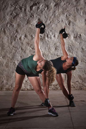Two pretty ladies women lifting kettlebell weights over their shoulders photo