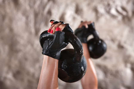 Womans hand holding kettlebell weight up in the air photo