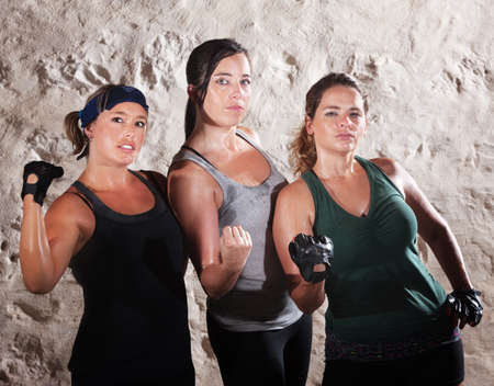 Three cute muscular women flexing their arms Stock Photo - 15934467
