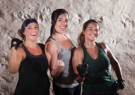 Three friends flexing their muscles in boot camp style workout Stock Photo