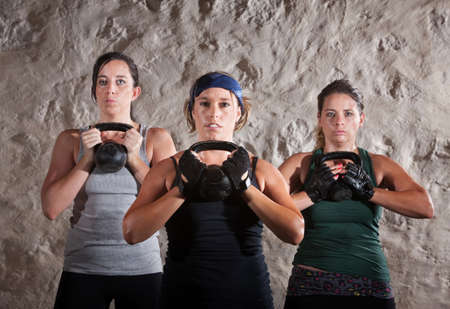 Serious women lifting kettlebells for boot camp style workout photo