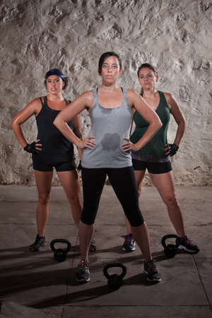 Strong trio of European women resting during boot camp workout photo