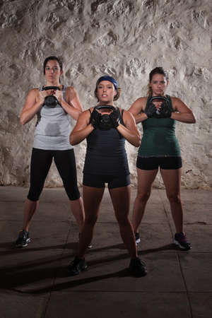 Three active females lifting large kettlebell weights photo