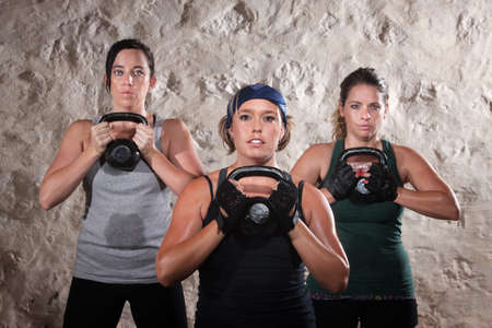 Serious group of three ladies lifting kettlebell weights photo