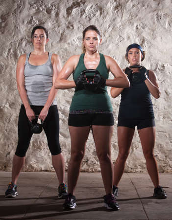 strong: Three strong women lifting kettlebell weights during boot camp workout
