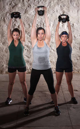 sweat girl: Three strong women lifting weights during boot camp workout