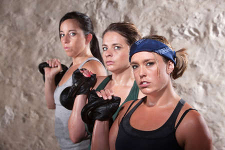 boot camp: Three pretty white women working out with kettlebell weights