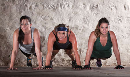 Sweating women doing push ups during bootcamp workout photo