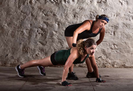 push ups: Bootcamp workout coach helps woman with push ups Stock Photo