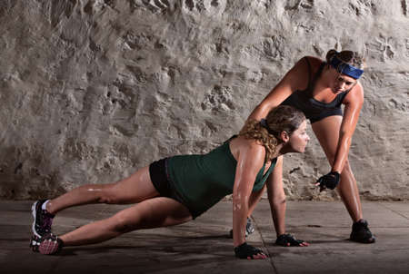 Boot camp training instructor helping lady with push-ups photo