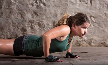 boot camp: One beautiful young woman doing push ups indoors