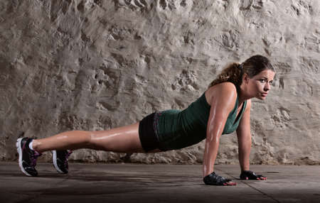Pretty woman doing push ups and sweating indoors photo