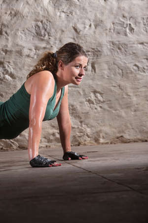 Young beautiful lady doing push ups indoors photo