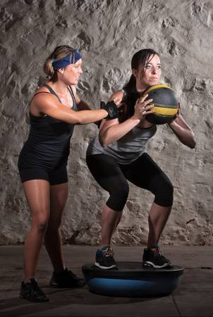 Pretty boot camp fitness instructor with lady on bosu photo
