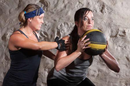 en cuclillas: Campamento de entrenamiento el entrenador serio arranque con bola atleta y la medicina