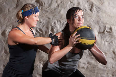 tough girl: Serious boot camp workout coach with athlete and medicine ball Stock Photo
