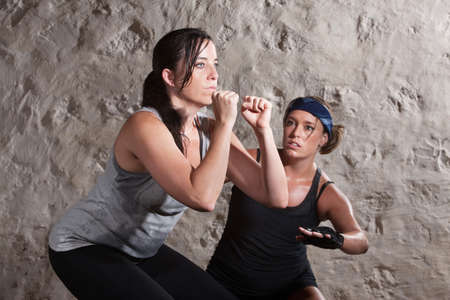 Caucasian athlete sweating with trainer in boot camp training workout photo