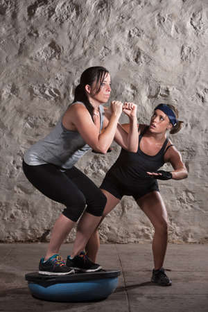 Lady squatting on bosu with boot camp training instructor watching Stock Photo - 16034869