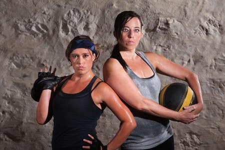Pair of beautiful women holding boot camp training equipment photo