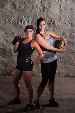 Two sweating young women posing with workout equipment photo