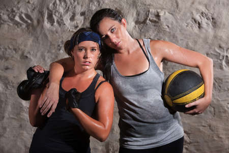 Strong Caucasian woman with workout partner flexing her bicep