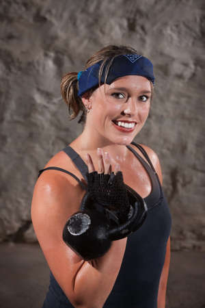 Smiling young woman sweating and lifting a kettle bell weights photo
