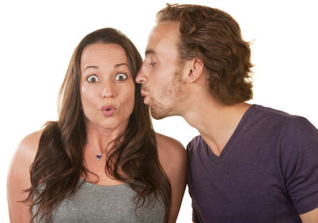 Astonished Caucasian woman kissed on cheek by man Stock Photo - 16300142