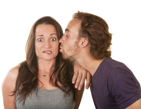 conflicted: Surprised woman being kissed by bearded white man Stock Photo