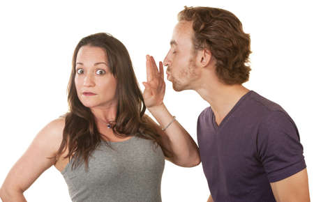 Unhappy woman blocking bearded mans kiss over white background