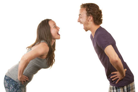 facing: Excited white couple with hands on hips facing each other