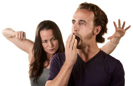 gullible: Woman winding up to punch yawning man Stock Photo