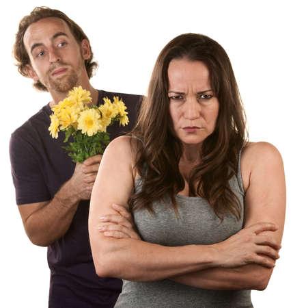 pardon: Angry jeune femme et l'homme au bouquet de fleurs Banque d'images