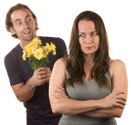 grumpy: Sceptische vrouw met lachende jonge man met bloemen Stockfoto