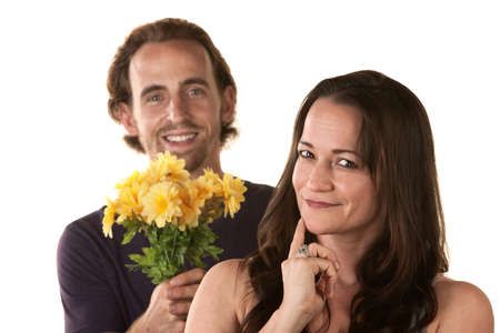 forgiving: Grinning woman and smiling man holding flowers Stock Photo