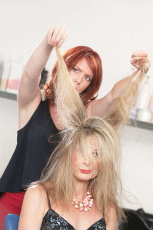 hair stylist: Annoyed hair stylist pulling on womans blond hair  Stock Photo
