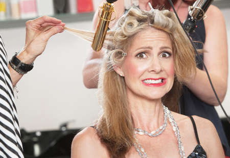 Anxious middle aged white woman with hair stylists working Stock Photo - 16578046