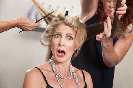 pulling hair: Hair stylists working around surprised blond woman