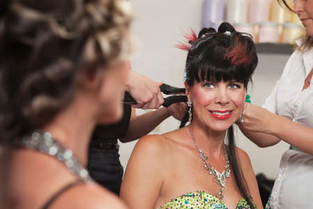 Smiling woman looking at lady with hair stylists working photo