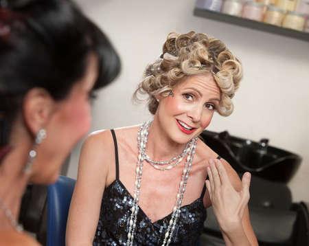 Two pretty women talking in hair salon photo